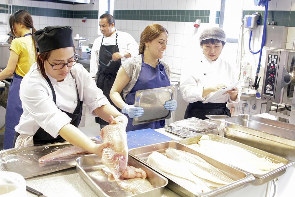 Tre kvinner med fiskefileer på et industrikjøkken.