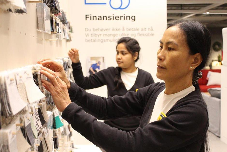 To kvinner med IKEA-navnelapper ser på stoffprøver på IKEA.
