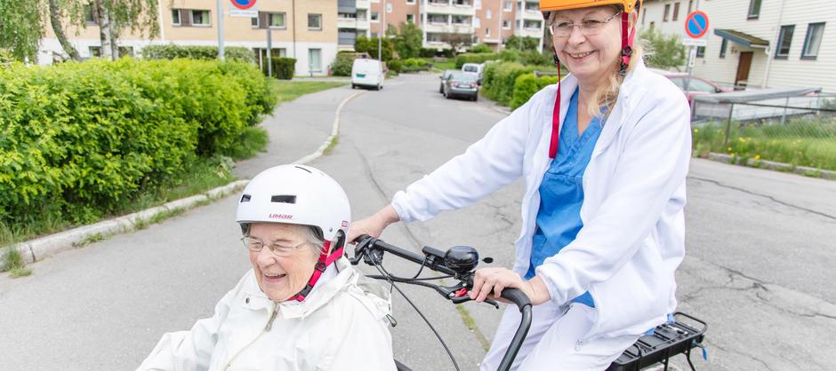 Beboer på sykkeltur med ansatt ved Abildsø sykehjem