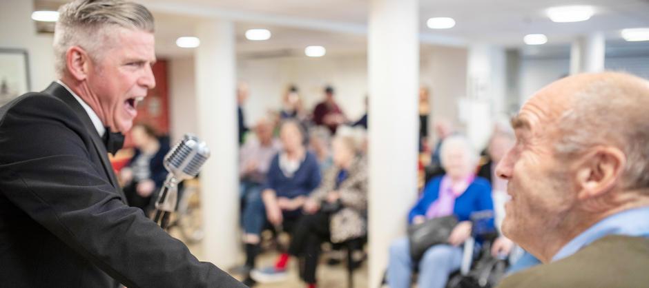 Nærbilde av mann i smoking som synger i en gammel mikrofon foran flere beboere på Abildsø sykehjem.