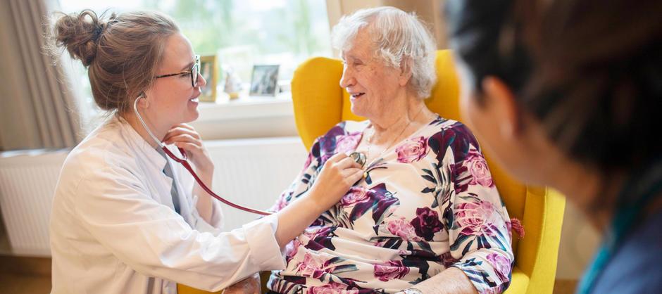 Lege smiler og lytter til brystet til en smilende eldre dame.