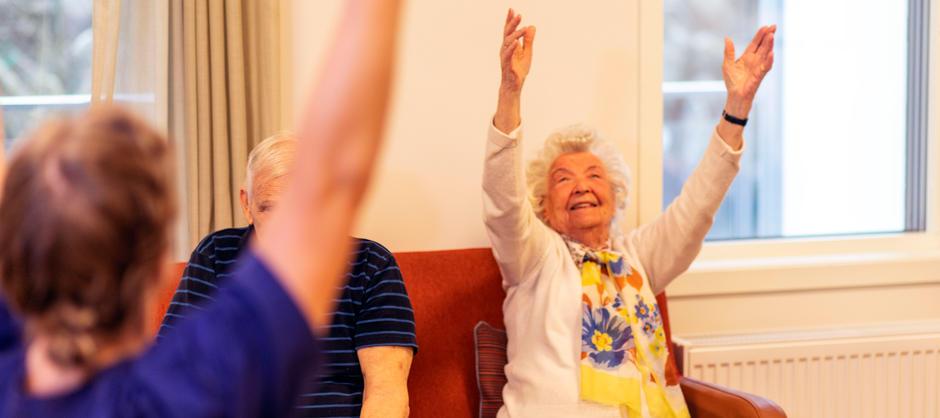 Beboer smiler og gjør bevegelsestrening ved å strekke to armer i været.