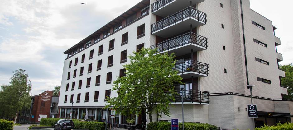 Bilde av inngangspartiet og forsiden av blokka til Vinderenbo- og servicesenter fra gaten.