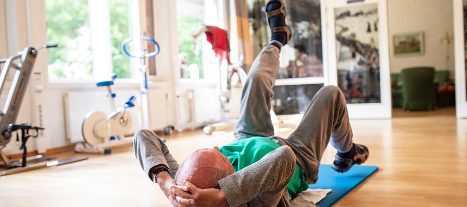 Mannlig beboer ligger på en blå treningsmatte ved siden av andre treningsapparater og strekker det ene benet til værs.