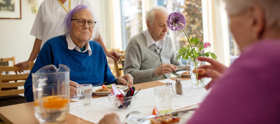 Tre beboere spiser mat med vannmugge, krydder og blomst på bordet.