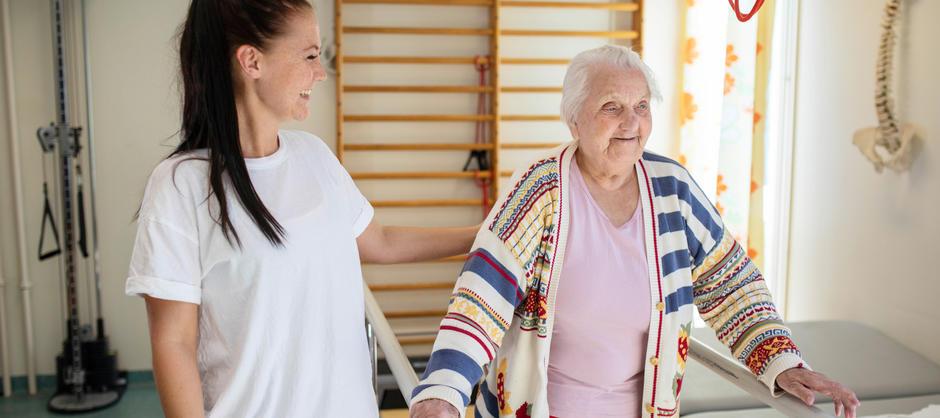 Eldre kvinne smiler og gjør balanseøvelse i et treningsrom sammen med ung smilende kvinne som støtter henne.