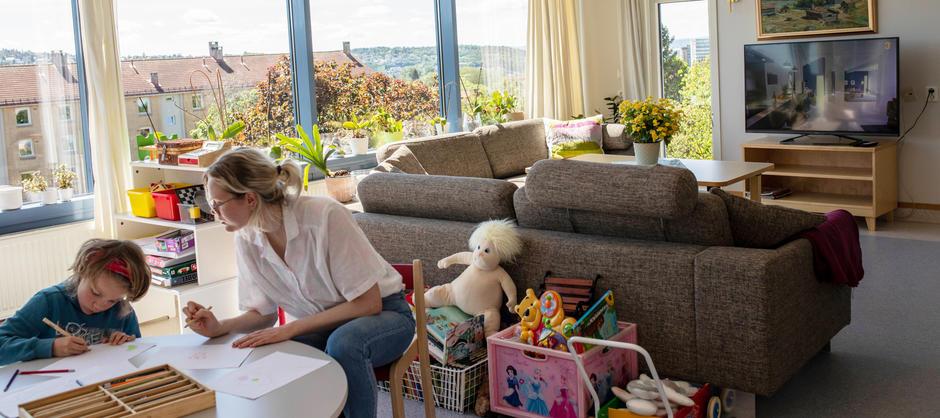 Et barn og en kvinne sitter i et lyst rom ved et barnebord og tegner, med andre leker og sofa og tv i bakgrunnen.