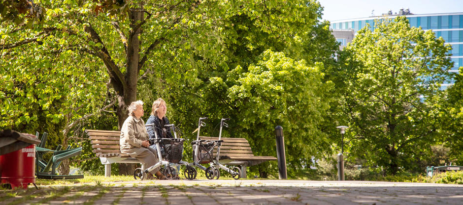 To eldre kvinner sitter ute på en benk med to gåstoler foran seg i en park med grønne trær i bakgrunnen.