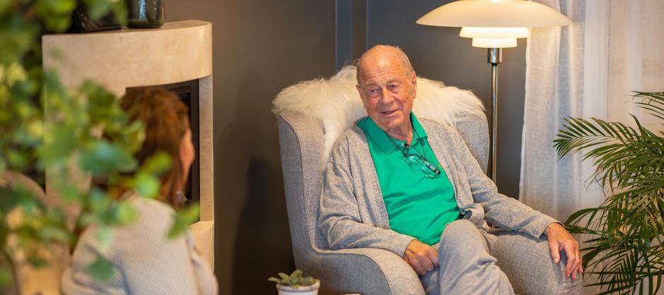 Beboer i samtale med pleier i lesekrok på Vinderen bo- og servicesenter.
