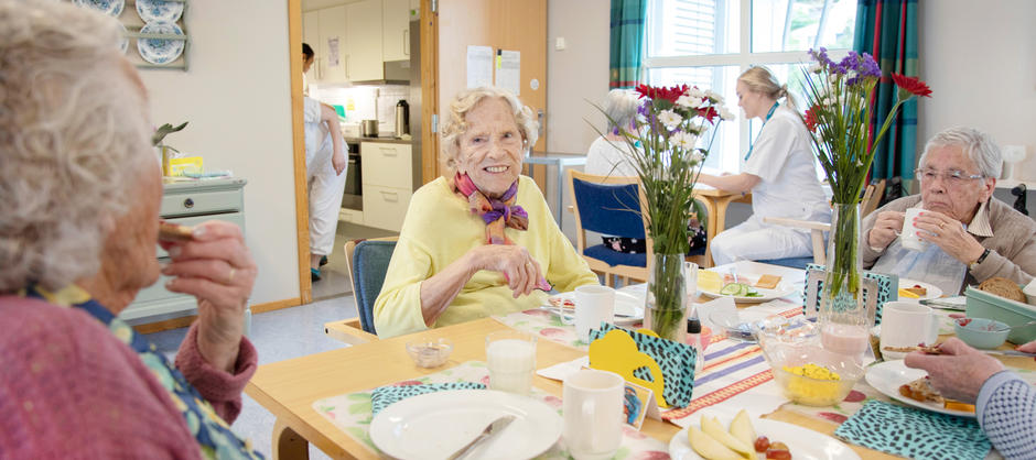 Beboere smiler og koser seg sammen med felles frokost med blomsterpynt på bordet.