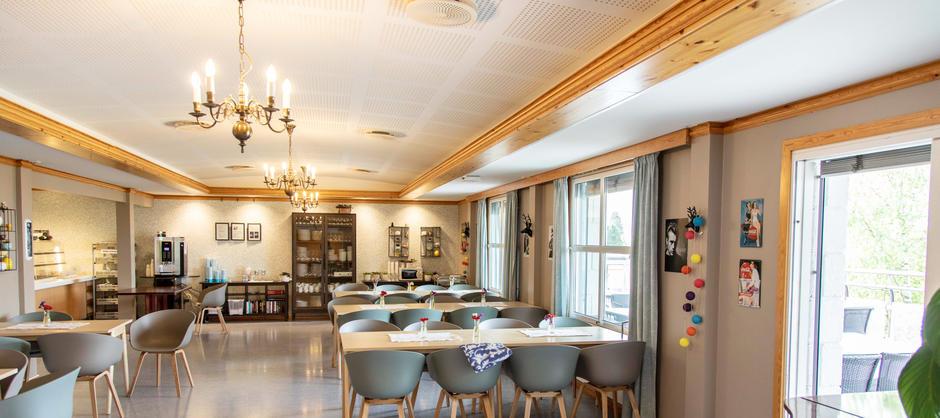 Bilde av interiøret i spisesal på Lillohjemmet med utgang til terrasse.