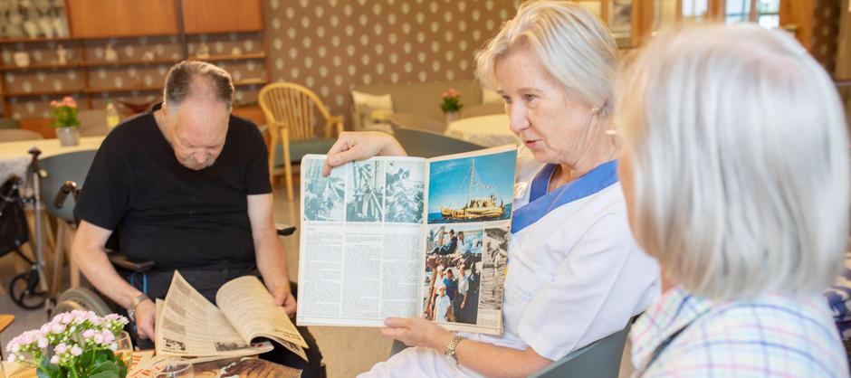En pleier leser og snakker om historier fra gamle blader for beboere.