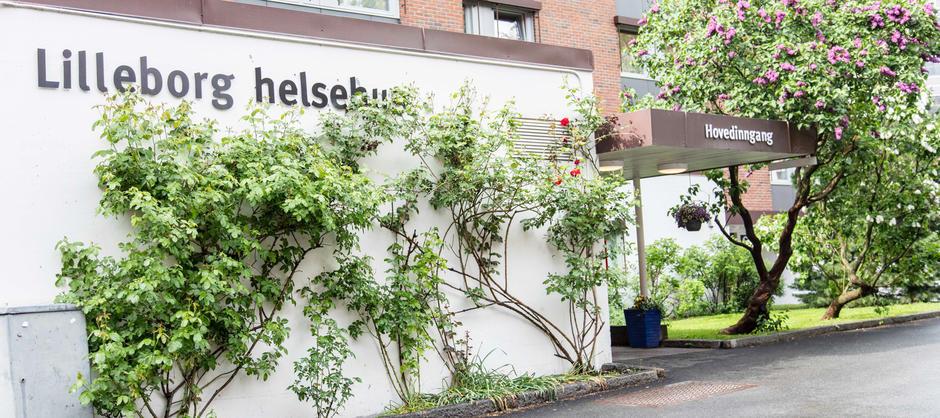 Bilde av inngangen til Lilleborg helsehus med grønne planter som vokser oppover veggen til bygget.