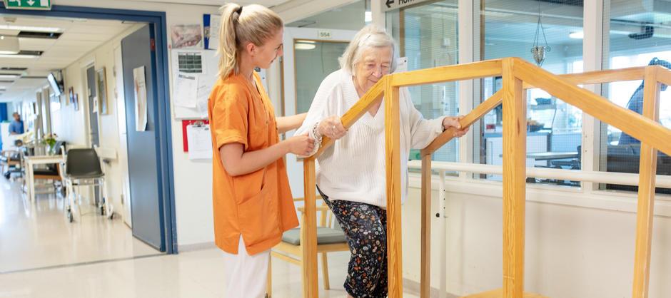 En dame smiler mens hun trener på å gå i trapp under veiledning og hjelp av fysioterapaut på Lilleborg helsehus.