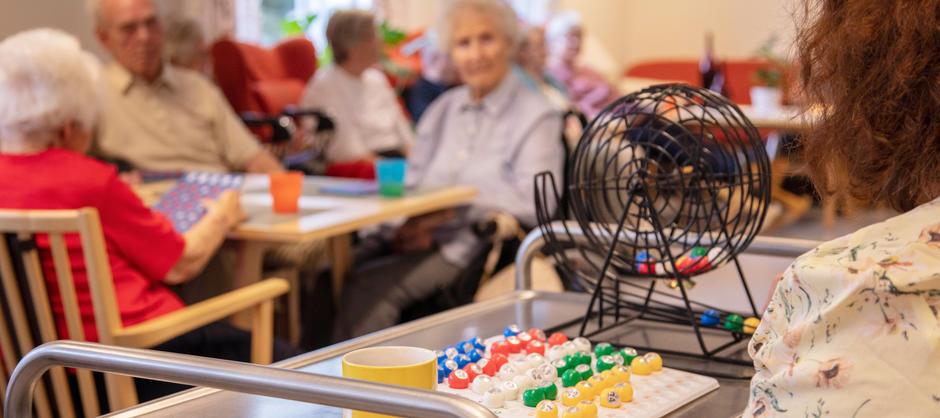 Nærbilde av bingorulle og bingokuler med beboere i bakgrunnen som spiller bingo i et fellesrom.