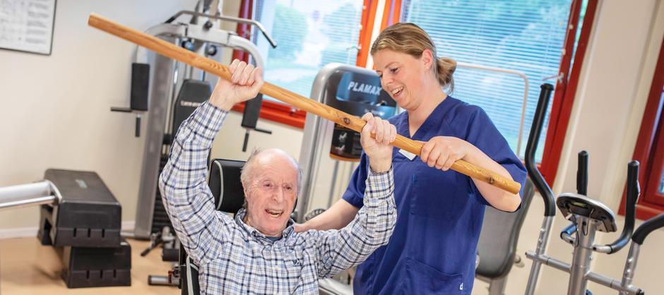 Beboer smiler mens han trener styrke sammen med fysioterapauten i et treningsrom.