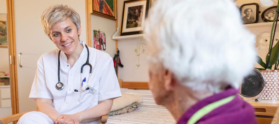 Bildet av lege som smiler i samtale med beboer.