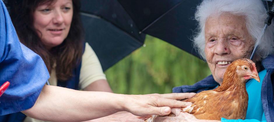 En beboer og pleiere smiler og koser med en høne.