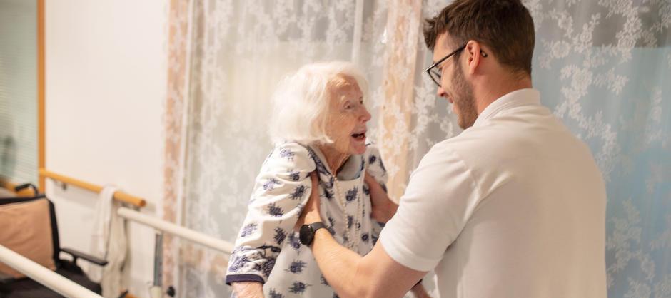 Fysioterapaut støtter opp beboer som smiler under bevegelsestrening.