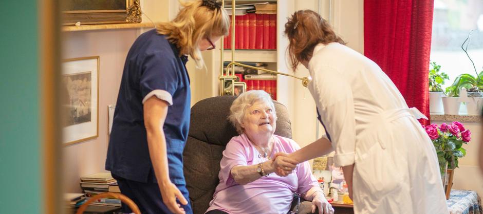 Lege og sykepleier håndhilser på beboer som smiler under visitt på beboerrom.