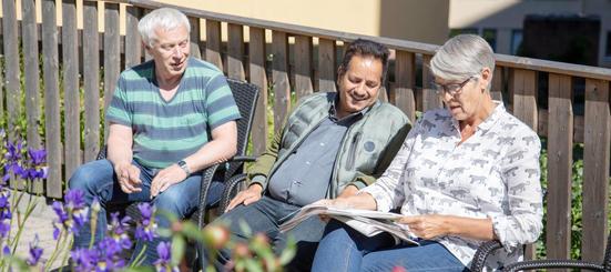 En ansatt sitter med to brukere av Villa Enerhaugen og leser quiz i hageområdet utenfor.