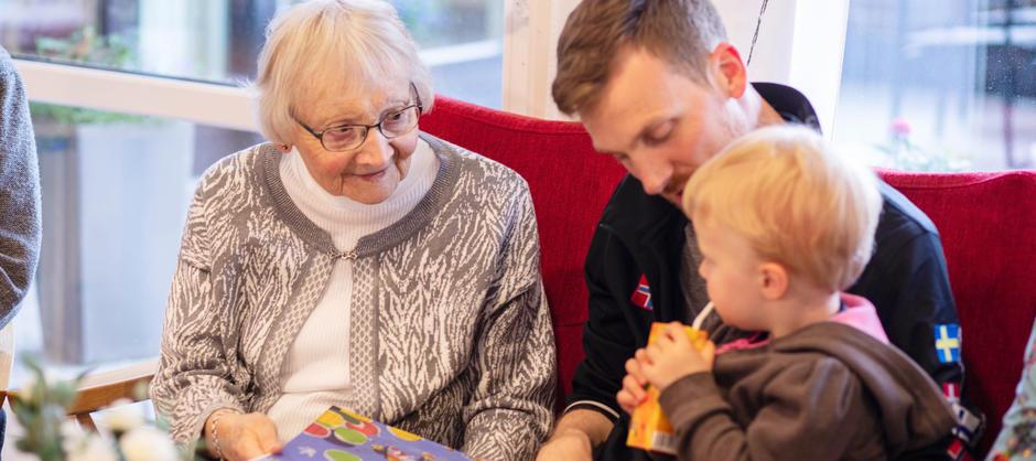 En beboer smiler og viser frem en bok til en pappa som er på besøk med barnet sitt for å hilse på de eldre ved Langerud sykehjem.