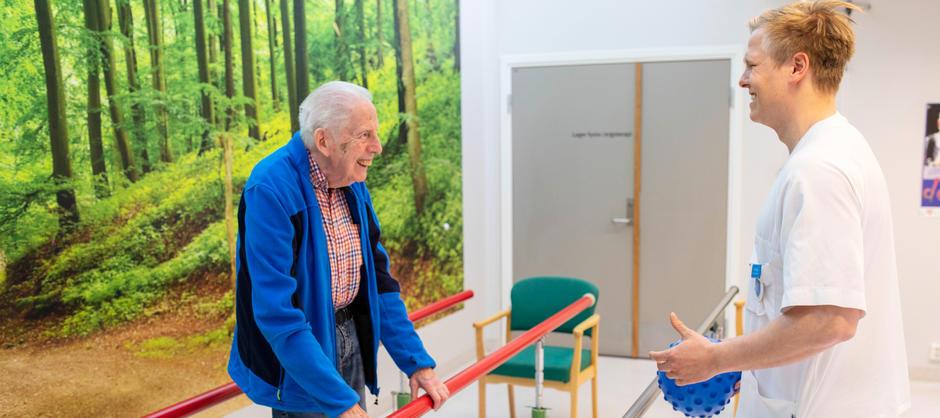 En beboer ved Langerud sykehjem trener balanse og ballkast med fysioterapaut som smiler i sykehjemmets trimrom.