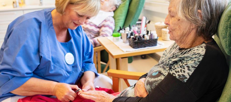 En kvinnelig beboer slapper av mens hun får stelt neglene av en pleier ved Langerud sykehjem.