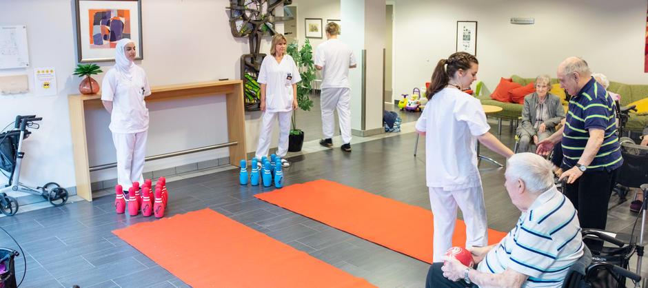 Beboere og ansatte ved Langerud sykehjem spiller bowling med myke baller i fellesområdet.