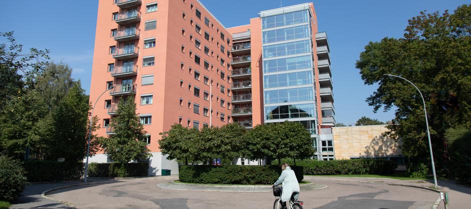 Akerselva sykehjem med grønne trær i sol sett fra gaten.