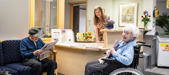 Bilde fra resepsjonen til Akerselva sykehjem med ansatt og beboere som ler og får utlevert dagens avis.