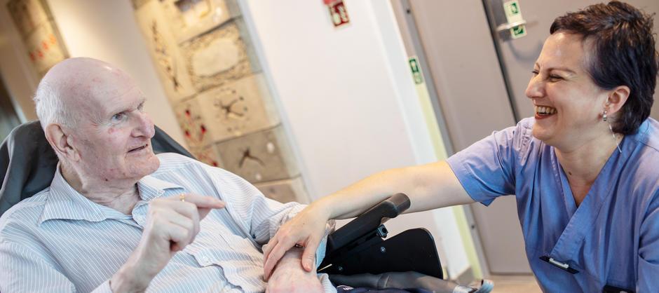 Beboer i rullestol forteller historier til pleier som smiler ved Akerselva sykehjem.