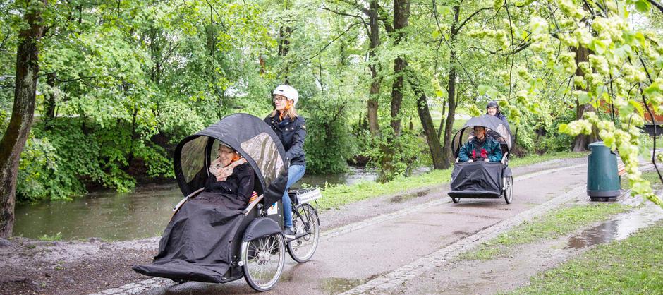 Beboere og ansatte på sykkeltur i grønne naturomgivelser langs Akerselva som ligger rett utenfor Akerselva sykehjem.