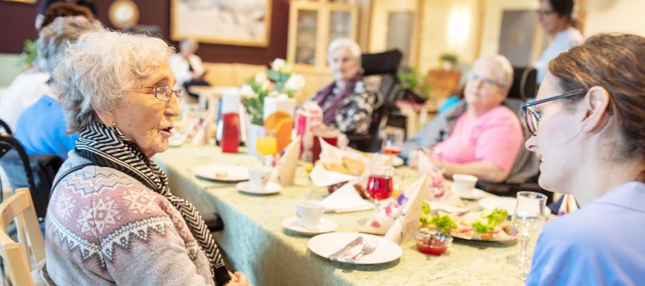 Bilde av beboere som spiser et måltid i felleskap og pleier som snakker med dame.