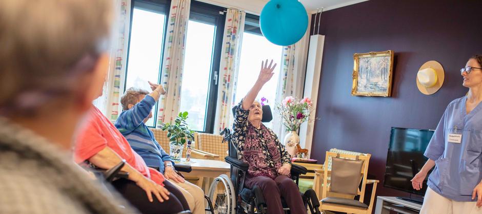 Beboere trener sammen med fysioterapaut på å slå en blå ballong opp i luften mens de sitter i ring på Stovnerskogen sykehjem.