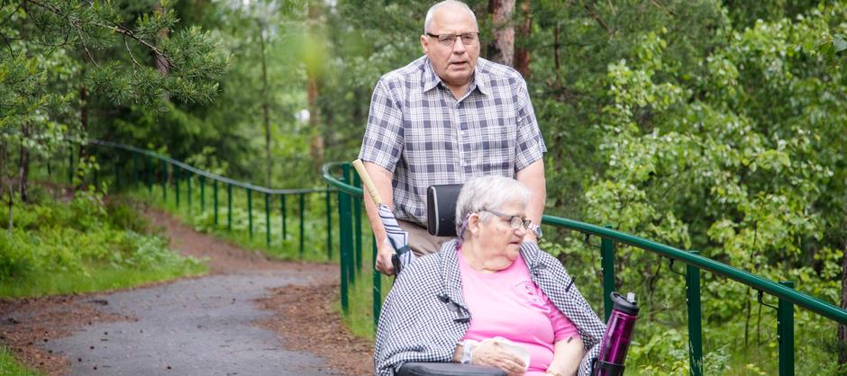 En mann triller sin kone i rullestol på de asfalterte gåstiene i grønne naturomgivelser utenfor Stovnerskogen sykehjem.