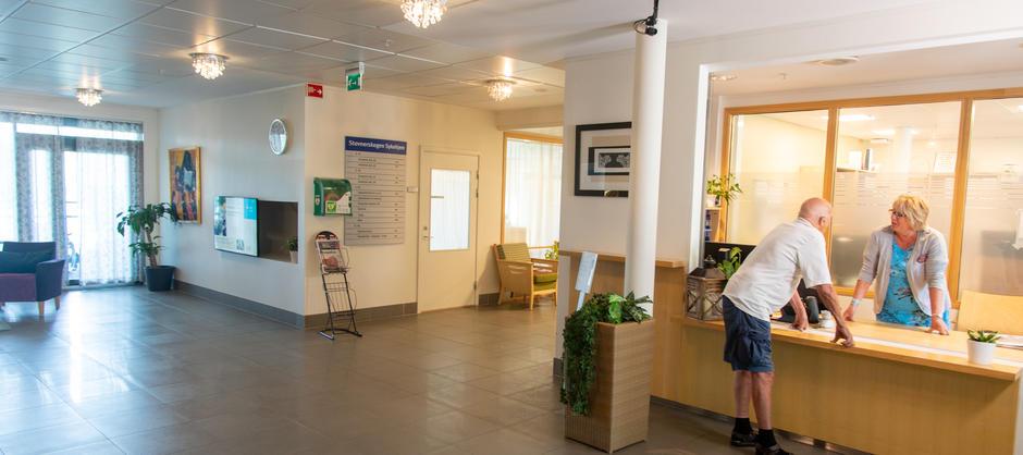 Bilde av beboer som snakker med ansatt i resepsjonen på Stovnerskogen sykehjem.