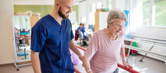 Fysioterapaut hjelper smilende pasient med gåtrening i helsehusets rehabiliteringsrom.