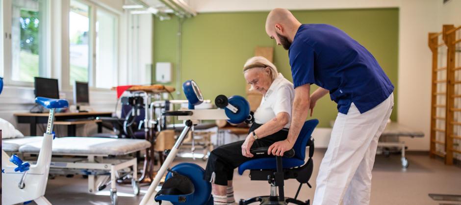 Bilde av fysioterapaut som hjelper pasient ned i stol der hun kan sykle på treningingsapparat i Ryen helsehus moderne treningsrom.