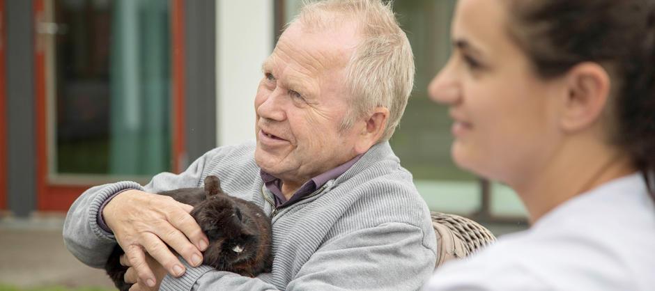 Mann koser med en kanin sammen med en pleier som sitter ved siden av ham.