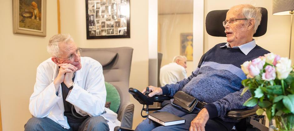 Bilde av en lege og en beboer som snakker sammen