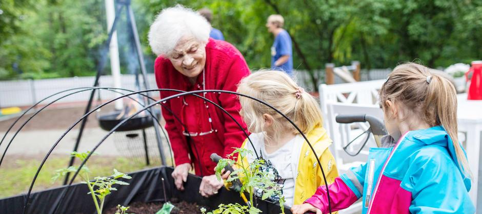 Bilde av beboer og barn ved plantekasse