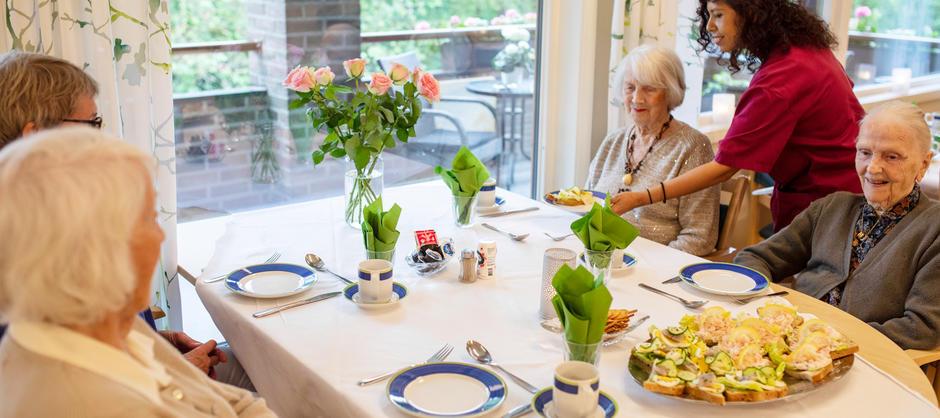 Bilde av beboere som får servert lunsj av en ansatt