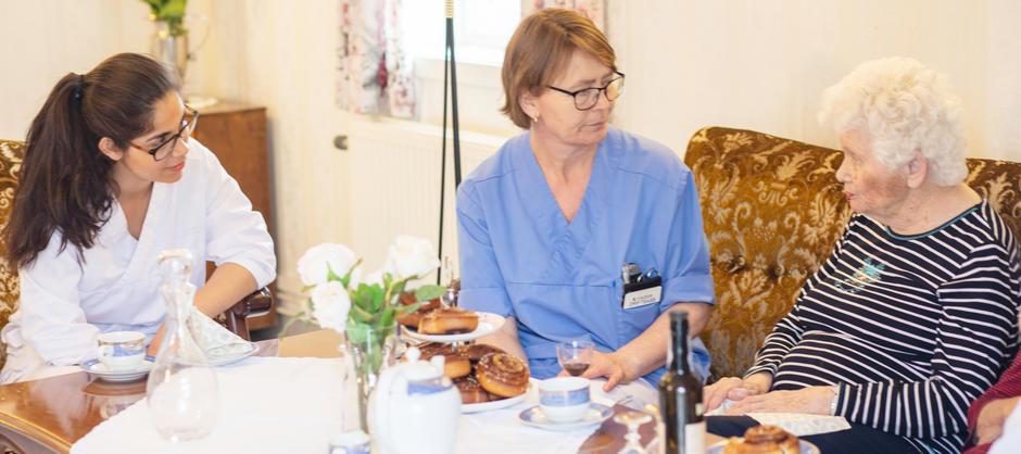 Bilde av kaffetreff mellom beboer og personale.