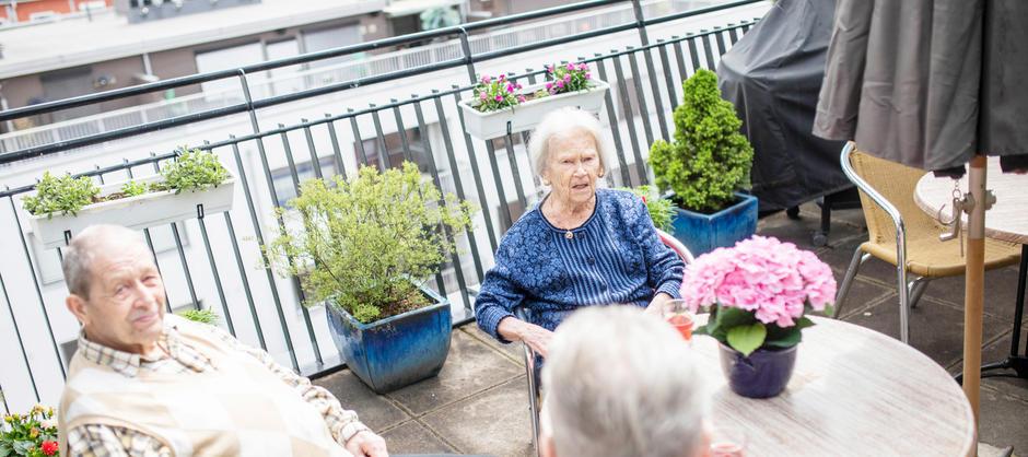 Bilde av to beboere som sitter ute på en balkong.