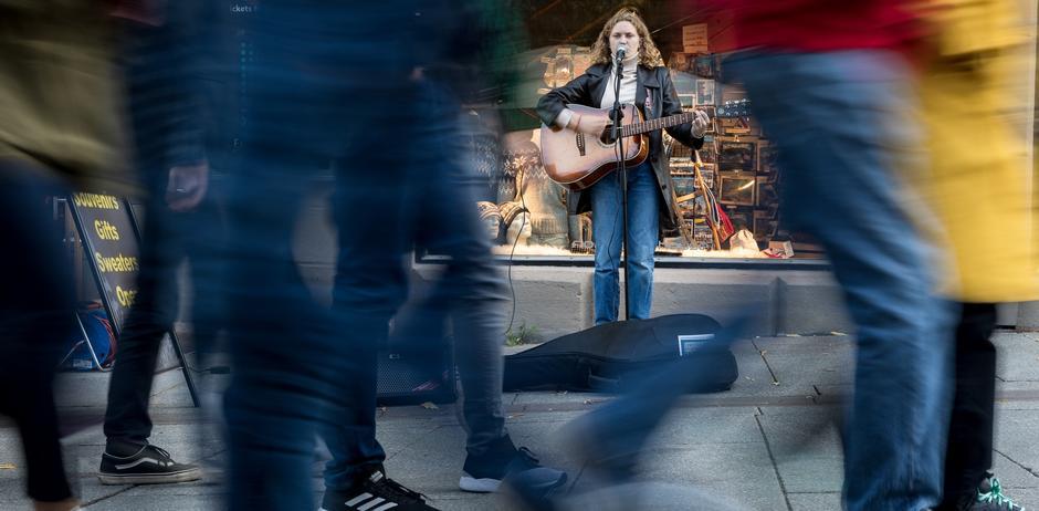 Kvinne spiller og synger på gaten, mange går forbi.