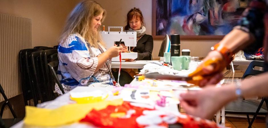 Kvinner sitter ved et hobbybord og syr og klipper.