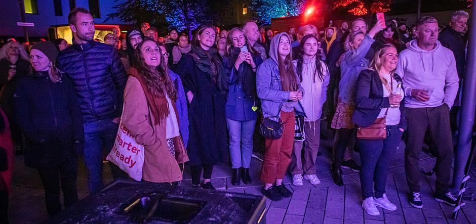 Publikum står ut og ser opp på scenen.