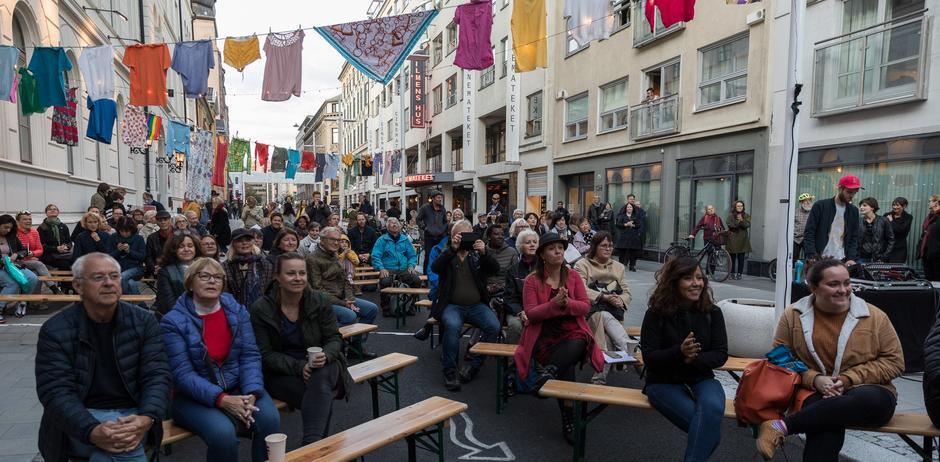 Publikum sitter på penger gjennom gaten mellom bygningen henger det mange klessnorer med klær.