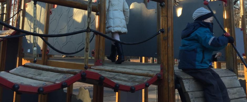 Gutt og jente leker i klatreborg